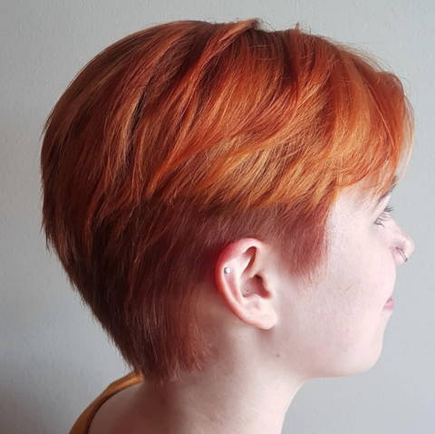 side view of a woman with a bright red pixie hair cut