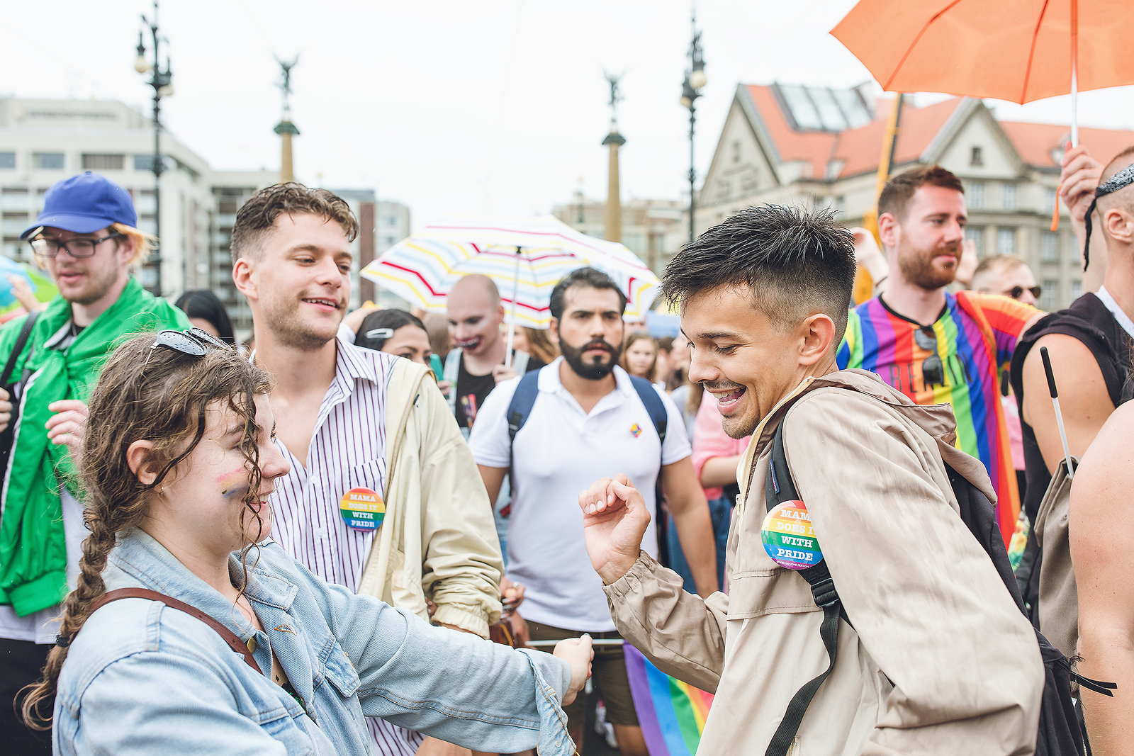 Image of a young man and woman with pride pins on their clothes, dancing in the street while others are walking around them with pride pins as well.