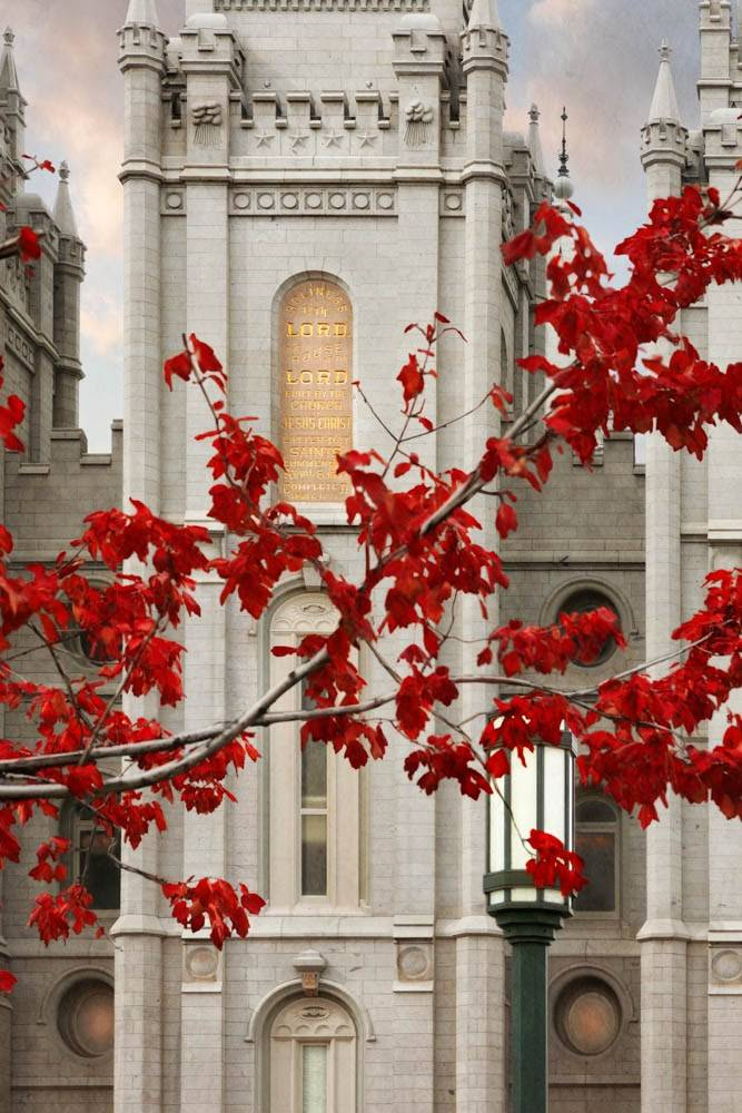 Vertical, up-close photo of the front of the Salt Lake City Utah Temple behind red leaves.
