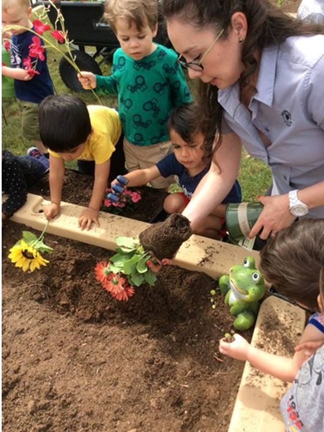 Image of children and teacher planting flowers