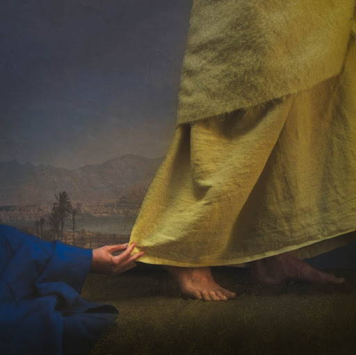 Image of woman's hand reaching out to touch Jesus' robe.