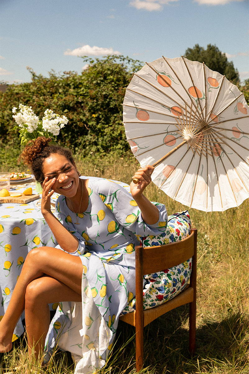 Miquita Oliver wear YOLKE Lemon Calamity Dress holding a parasol and sitting at a table in a field of flowers