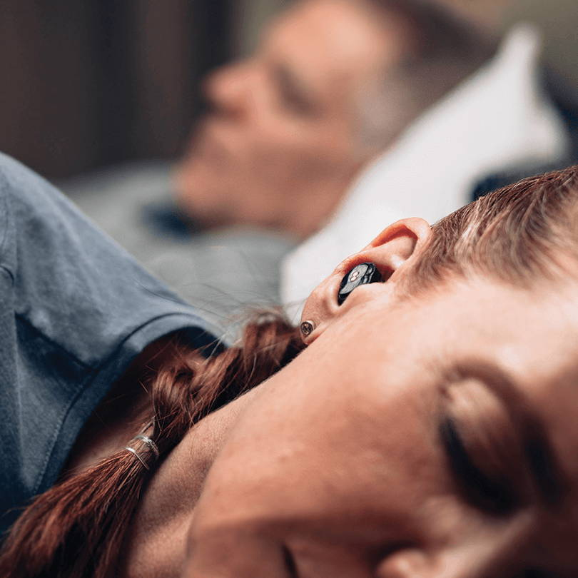 couple in bed with earbuds in use while partner snores