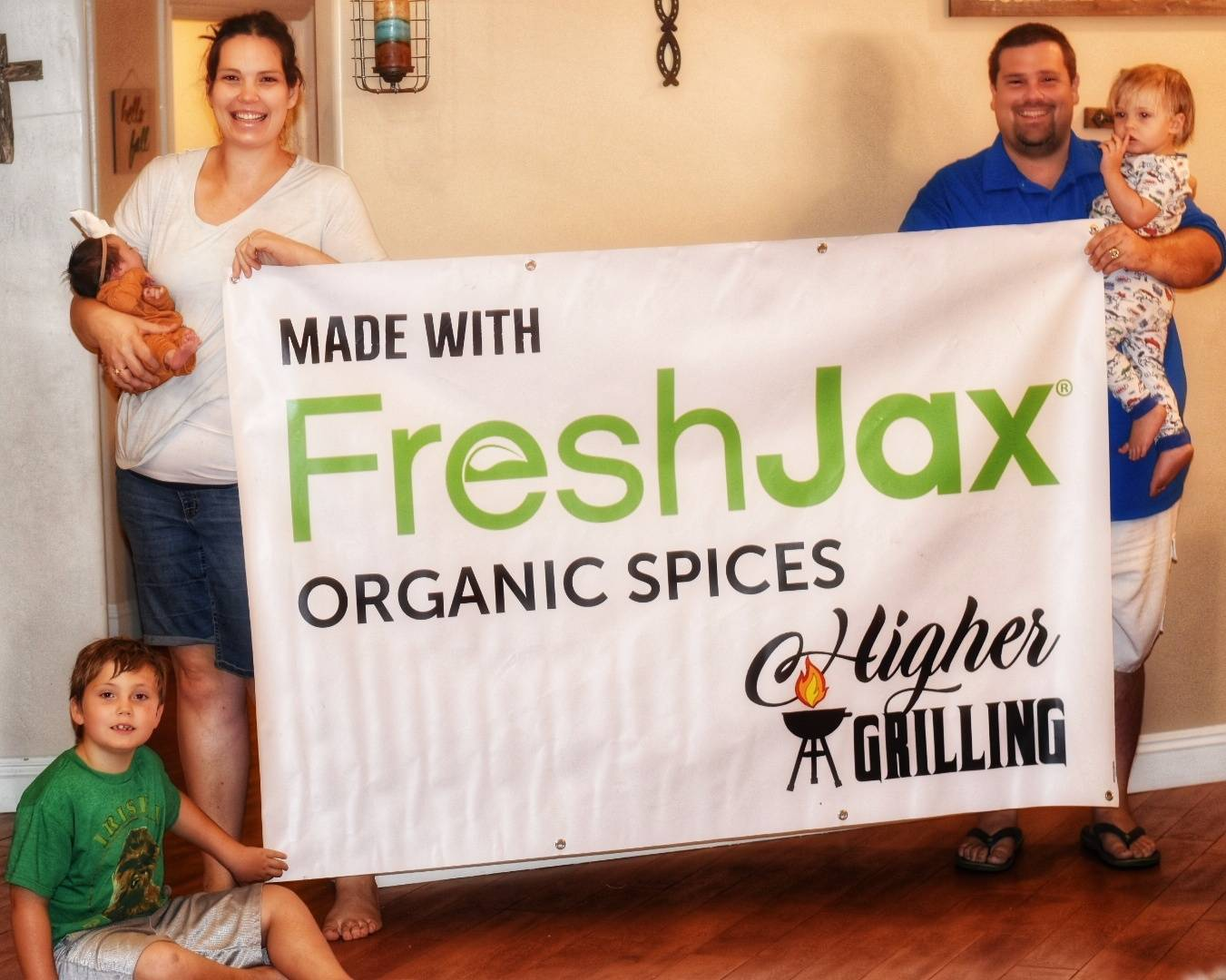 """Higher Grilling BBQ Family Holding Sign that Reads """"Made with FreshJax Organic Spices"""""""