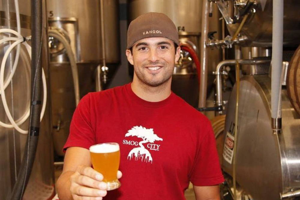 Jason is holding out a taster of beer, smiling with a backwards hat on in the middle of the fermentation tanks. He is wearing a red smog city logo t shirt.