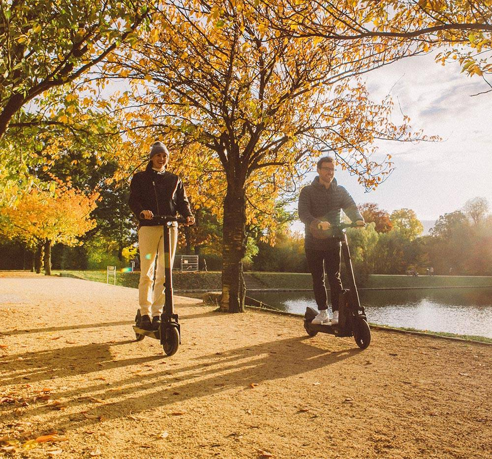 okai-es200-escooter-couple-riding-scooters-autumn-path-mobile