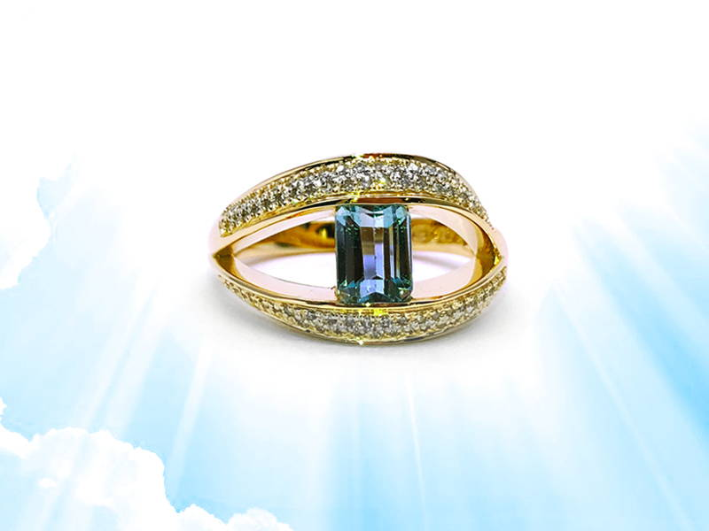Yellow gold ring with a large opening paved with small diamonds linked by an emerald cut blue topaz.