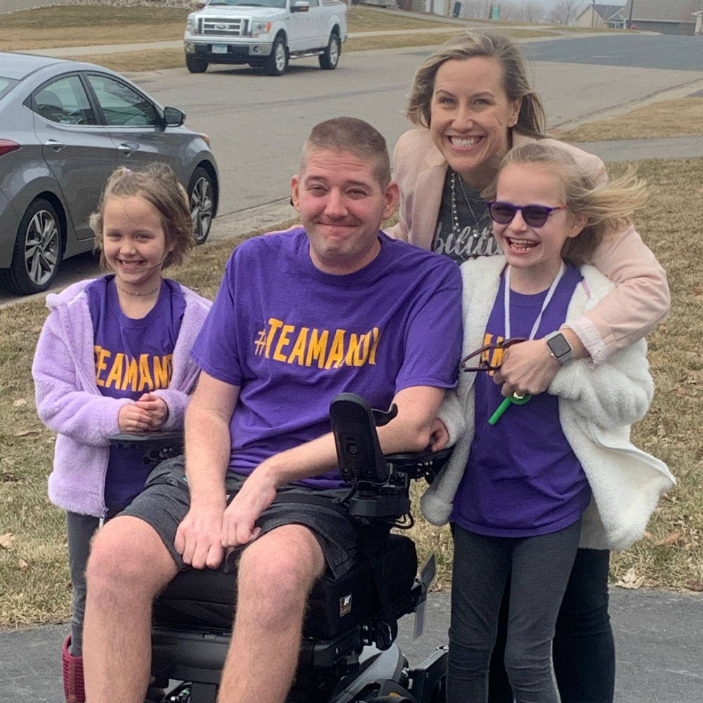 """A photo of our April 2019 Hero, Andy McBride, and his wife and two daughters. They are wearing shirts that say """"Team Andy"""" on them and are posing on their driveway the day Andy returned home from the hospital."""