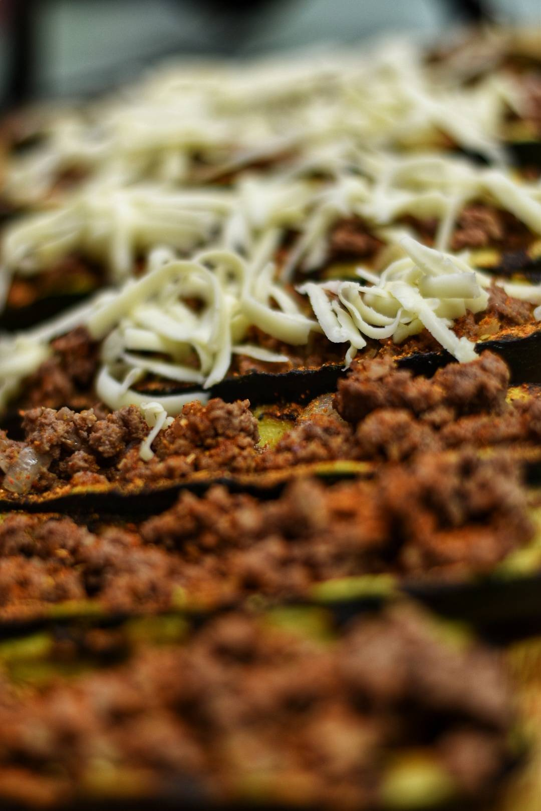 Grilled zucchini with ground beef and shredded cheese